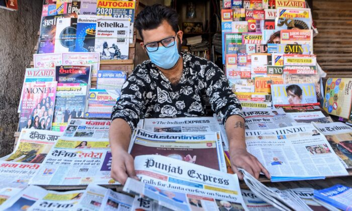 A vendor wearing a mask displays newspapers at his stall in Amritsar, a city in India, on March 20, 2020. (Narinder Nanu/AFP via Getty Images)