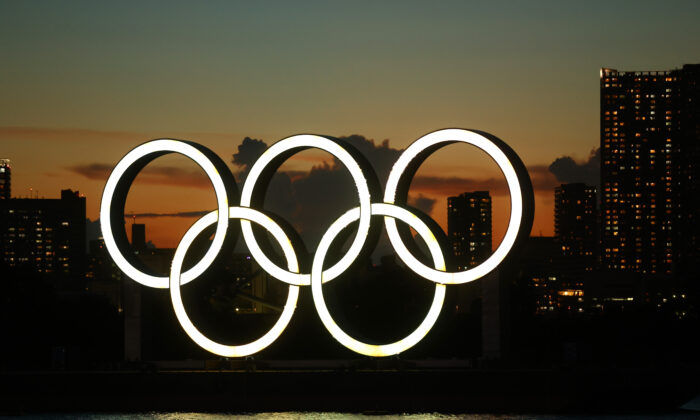 A general view of the Olympic rings installation and Rainbow Bridge as the sun sets on day twelve of the Tokyo 2020 Olympic Games at Odaiba Marine Park in Tokyo on Aug. 4, 2021. (Clive Rose/Getty Images)