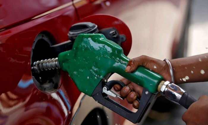 A worker holds a nozzle to pump petrol into a vehicle at a fuel station in Mumbai, India on May 21, 2018. (Francis Mascarenhas/Reuters)
