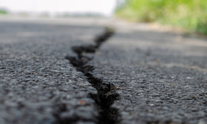 It's important to keep cracks in asphalt as filled and closed as possible; if water seeps in, it will make the base unstable. (NARENTHORN/Shutterstock)