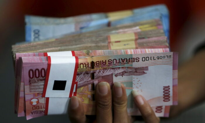 An employee of a money changer holds a stack of Indonesia rupiah notes before giving it to a customer in Jakarta, Indonesia, on Oct. 8, 2015.  (Beawiharta/Reuters)