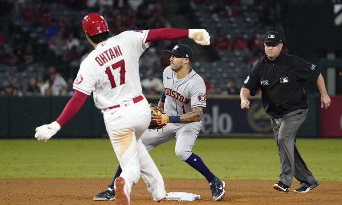 Los Angeles Angels designated hitter Shohei Ohtani, left, steals second as Houston Astros shortstop Carlos Correa, center, waits for the throw while second base umpire Todd Tichenor watches during the sixth inning of a baseball game in Anaheim, Calif., on Sept. 23, 2021. (AP Photo/Mark J. Terrill)