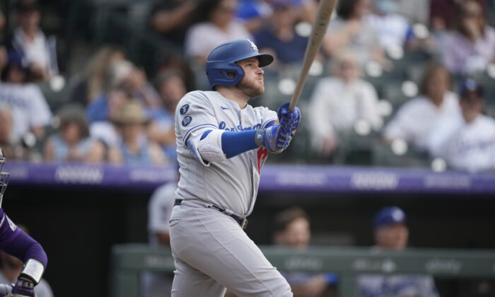 Los Angeles Dodgers' Max Muncy follows the flight of his two-run home run off Colorado Rockies relief pitcher Lucas Gilbreath in the 10th inning of a baseball game in Denver on Sept. 23, 2021. (AP Photo/David Zalubowski)