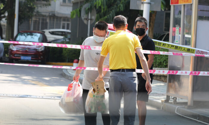 Residents transfer daily necessities at a residential area under tight restrictions due to cases of the COVID-19 virus in Xiamen in China's eastern Fujian province on Sept. 14, 2021. (STR/AFP via Getty Images)