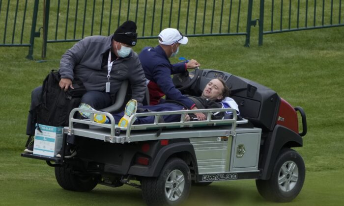 Actor Tom Felton is helped after collapsing on the 18th hole during a practice day at the Ryder Cup at the Whistling Straits Golf Course in Sheboygan, Wis., on Sept. 23, 2021. (Ashley Landis/AP Photo)
