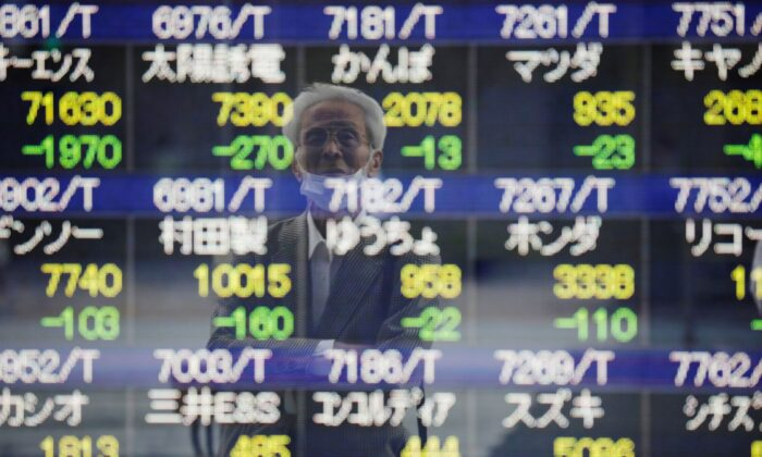 A man wearing a protective mask, amid the COVID-19 outbreak, is reflected on an electronic board displaying stock prices outside a brokerage in Tokyo, Japan on Sept. 21, 2021. (Kim Kyung-Hoon/Reuters)