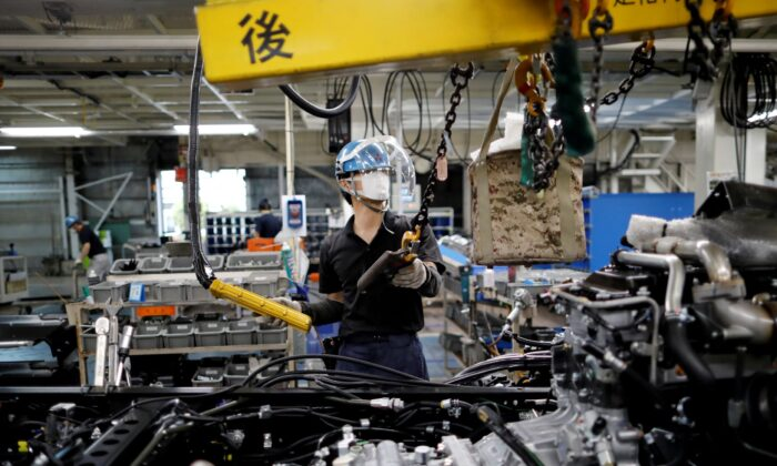 An employee wearing a protective face mask and face guard works on the automobile assembly line at Kawasaki factory of Mitsubishi Fuso Truck and Bus Corp, owned by Germany-based Daimler AG, in Kawasaki, south of Tokyo, Japan on May 18, 2020. (Issei Kato/Reuters)