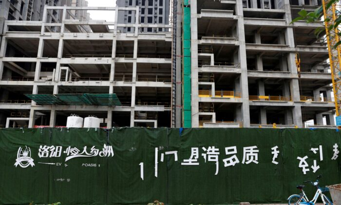 A peeling logo of the Evergrande Oasis, a housing complex developed by Evergrande Group, is seen outside the construction site where the residential buildings stand unfinished, in Luoyang, China on Sept. 16, 2021. (Carlos Garcia Rawlins/Reuters)