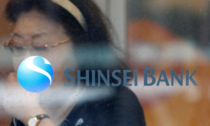 A woman walks past a logo of the Shinsei Bank at its branch in Yokohama, south of Tokyo, Japan on June 23, 2010. (Issei Kato/Reuters)