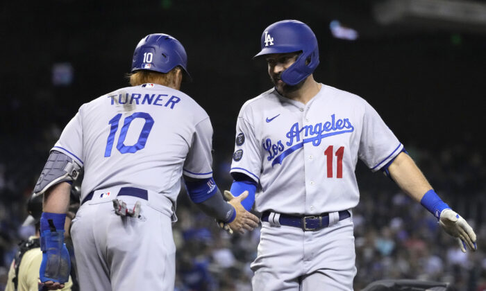 Los Angeles Dodgers' AJ Pollock celebrates with Justin Turner (10) after hitting a two-run home run against the Arizona Diamondbacks in the second inning during a baseball game, Friday, Sept. 24, 2021, in Phoenix. (Rick Scuteri/AP Photo)