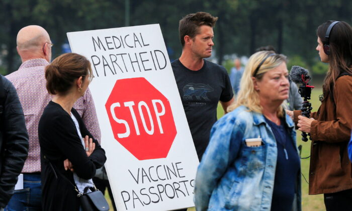 """People take part in a protest on the day the Dutch authorities introduce a mandatory """"corona pass"""", proof of the coronavirus disease (COVID-19) vaccination or a negative test result, to enter bars, restaurants, and cultural events in the country, in The Hague, Netherlands, on Sept. 25, 2021. (Eva Plevier/Reuters)"""