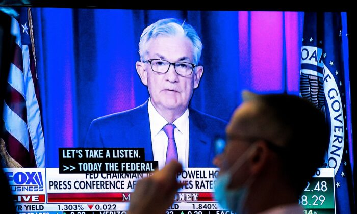 A screen displays a statement by Federal Reserve Chair Jerome Powell following the Federal Reserve's announcement as a trader works on the trading floor of the New York Stock Exchange (NYSE) in New York City on Sept. 22, 2021. (Brendan McDermid/Reuters)