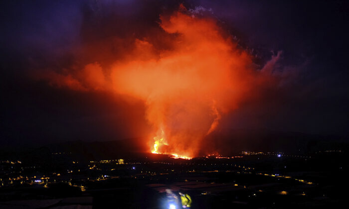 Two people walk as lava spews from a volcano on the Canary island of La Palma, Spain, in the early hours of Sept. 25, 2021. (Daniel Roca /AP Photo)