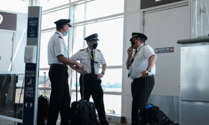 Pilots talk after exiting a Delta Airlines flight at the Ronald Reagan National Airport,  in Arlington, Va., on July 22, 2020. (Michael A. McCoy/Getty Images)