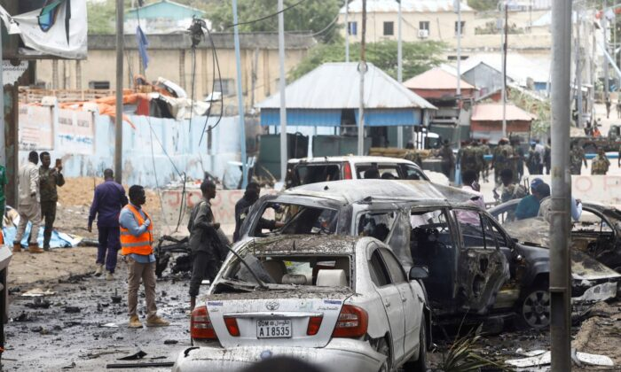 Civilians and Somalian security officers gather at the scene of a suicide car bomb at a street junction near the president's residence, in Mogadishu, Somalia, on Sept. 25, 2021. (Feisal Omar/Reuters)