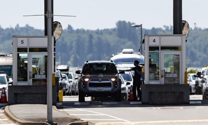 A Canada Border Services Agency officer hands documents back to a motorist entering Canada at the Douglas-Peace Arch border crossing, in Surrey, B.C., on Aug. 9, 2021. (The Canadian Press/Darryl Dyck)