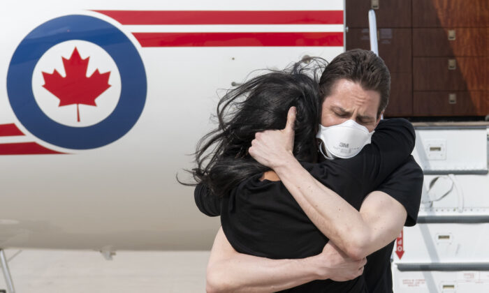 Former diplomat Michael Kovrig embraces his wife, Vina Nadjibulla, upon his arrival at Toronto Pearson International Airport on Sept. 25, 2021. (DND-MDN Canada/Cpl. Justin Dreimanis)