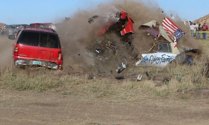 Daredevil John Smith, known as the Flying Farmer, crashes his Chevrolet Caprice while attempting a jump, in Makoti, N.D., on Sept. 25, 2021. (Hunter Andes/The Bismarck Tribune via AP)
