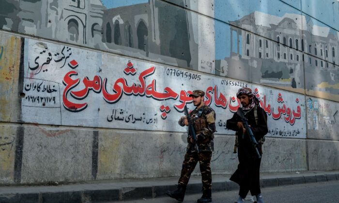 Taliban fighters patrol along a road on the backdrop of a mural pained on the wall of a flyover in Kabul on September 26, 2021. (Hoshang Hashimi/AFP via Getty Images)