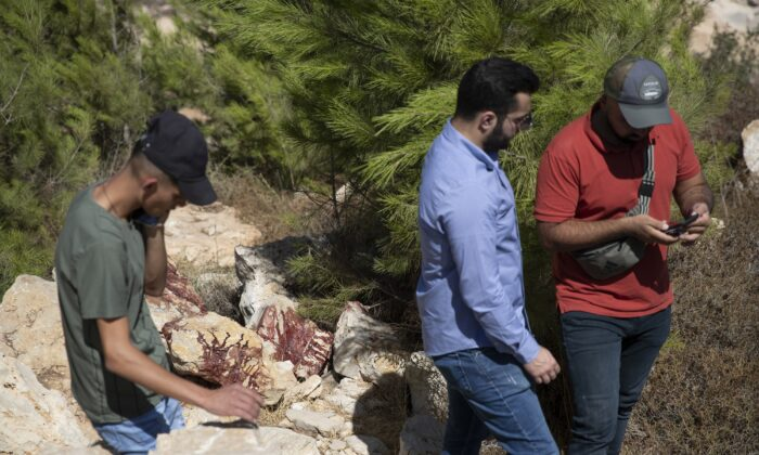 Locals inspect a bloodstained site after an Israeli anti-terrorist operation that killed five men, most confirmed Hamas terrorist members, in the West Bank village of Beit Anan, west of Ramallah, on Sept. 26, 2021. (Nasser Nasser/AP Photo)