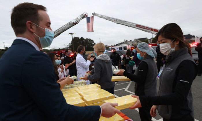 In this file photo, nurses at Kaiser Hospital are given boxes of See's candy as they leave the hospital at the end of their shift in South San Francisco, Calif., on May 14, 2020.  (Photo by Justin Sullivan/Getty Images)
