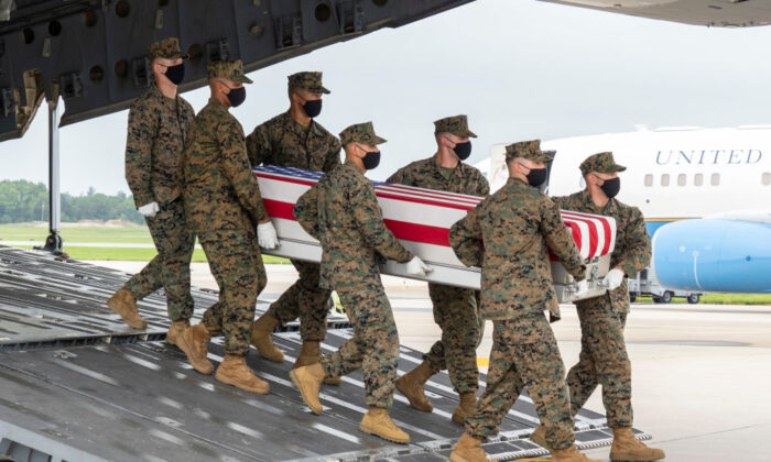A U.S. Marine Corps carry team transfers the remains of Marine Corps Lance Cpl. Dylan R. Merola of Rancho Cucamonga, California, Aug. 29, 2021 at Dover Air Force Base, Delaware. Merola was assigned to 2nd Battalion, 1st Marine Regiment, 1st Marine Division, I Marine Expeditionary Force, Camp Pendleton, California. (Jason Minto/U.S. Air Force via Getty Images)