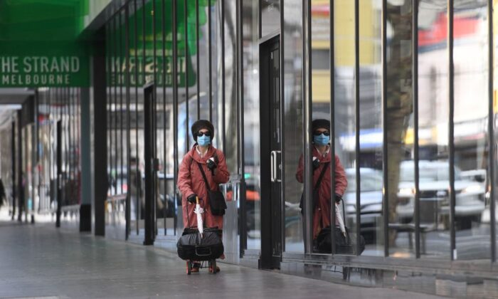 A woman walks along a quiet street in Melbourne's central business district in Australia, on August 11, 2021. (William West/AFP via Getty Images)