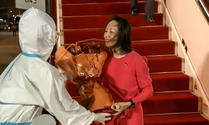 This screen grab made from video by Chinese state broadcaster CCTV shows Huawei executive Meng Wanzhou receiving flowers after she arrived in Shenzhen, Guangdong province, China, released on Sept. 25, 2021. (-/CCTV/AFP via Getty Images)