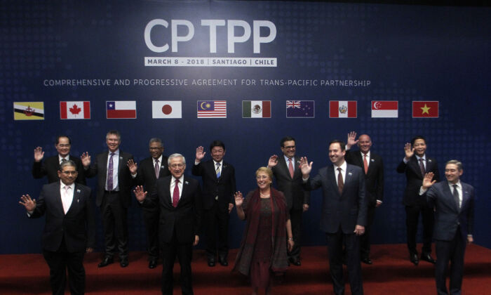 Foreign Affairs Ministers from member states wave as they pose for the official picture before signing the rebranded 11-nation Pacific trade pact, the Comprehensive and Progressive Agreement for Trans-Pacific Partnership (CPTPP), in Santiago, Chile, on March 8, 2018. (CLAUDIO REYES/AFP via Getty Images)