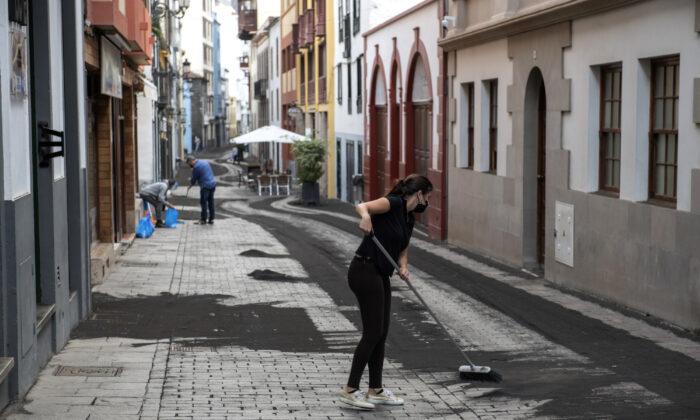 Residents clean the ash from the street in Santa Cruz de la Palma on the Canary island of La Palma, Spain, on Sept. 27, 2021. (Saul Santos/AP Photo)