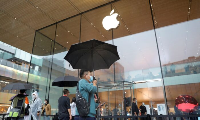 People wearing face masks at an Apple Store on the day the new Apple iPhone 13 series went on sale, in Beijing, China on Sept. 24, 2021. (Carlos Garcia Rawlins/Reuters)