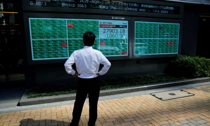 A man watches an electric board showing Nikkei index outside a brokerage at a business district in Tokyo, Japan on June 21, 2021. (Kim Kyung-Hoon/Reuters)