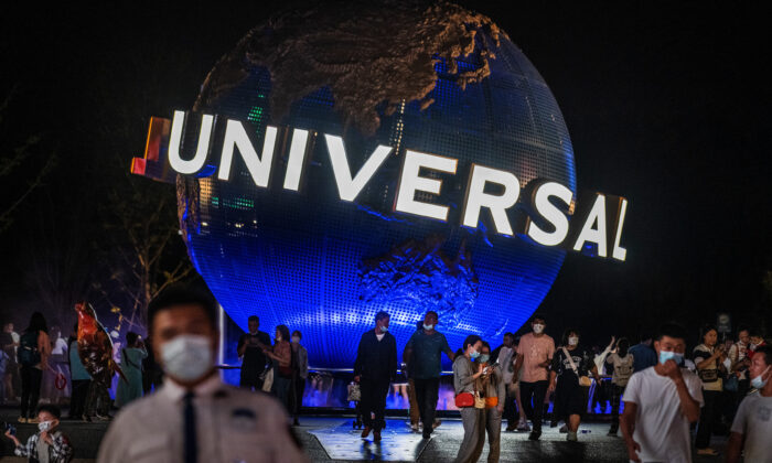 People walk in front of the trademark globe at Universal Studios Beijing city-walk in Beijing, China, on Sept. 23, 2021. (Kevin Frayer/Getty Images)