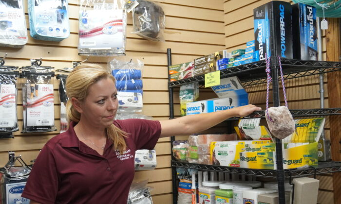 Amy Jonson, vice president of The Western Ranchman in Phoenix, Arizona, points to the empty shelf space that contained ivermectin for horses. The product is now sold out, due to demand from many customers who believe it's an effective treatment against COVID-19. (Allan Stein/Epoch Times)