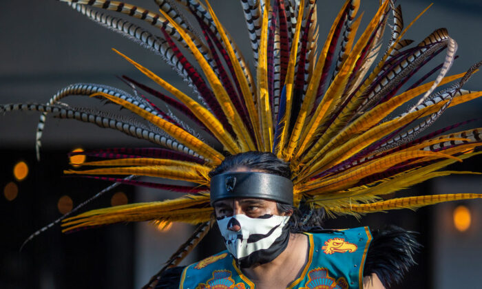 An Aztec dancer participates in a march in Los Angeles, on May 1, 2019. (David McNew/Getty Images)