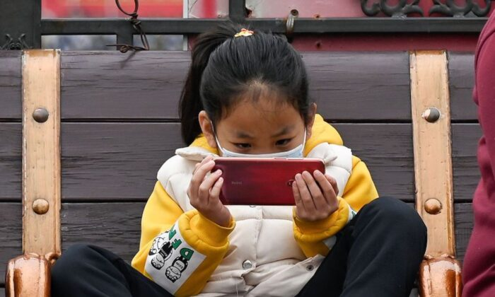 A girl watches a mobile phone as she rests on a bench in Beijing on March 4, 2021. (Wang Zhao/AFP via Getty Images)