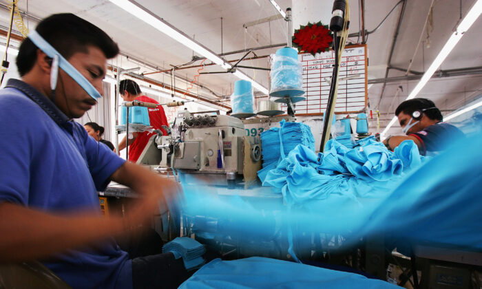 An employee tosses a garment onto a stack after sewing his portion of it at the a garment factory in Los Angeles, California, on Dec. 14, 2004. (David McNew/Getty Images)