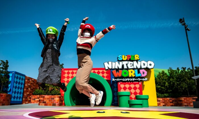Fans of Universal Studio Japan pose at the entrance of the Super Nintendo World, during a media preview of the theme park in Osaka, Japan, on March 17, 2021. (Philip Fong/AFP via Getty Images)