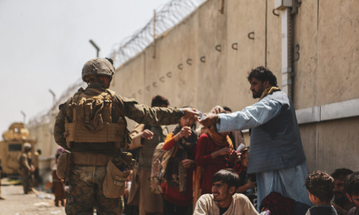 A U.S. Marine passes out water during the evacuation at Hamid Karzai International Airport  in Kabul, Afghanistan, on Aug. 21, 2021. (U.S. Marine Corps/Isaiah Campbell/Getty Images)