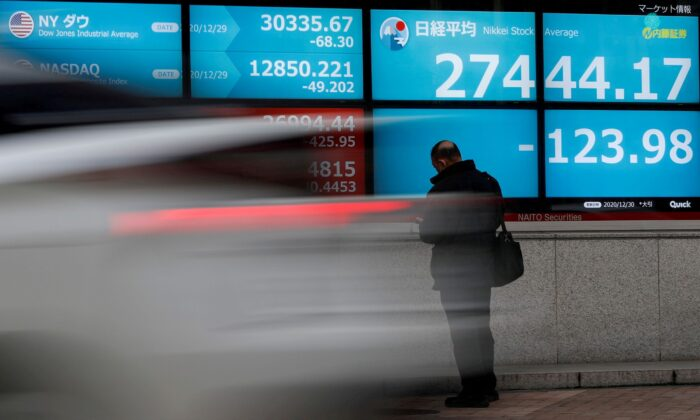 A man stands in front of a screen displaying Nikkei share average and the world's stock indexes outside a brokerage, amid the coronavirus disease (COVID-19) outbreak, in Tokyo, Japan on Dec. 30, 2020. (Issei Kato/Reuters)