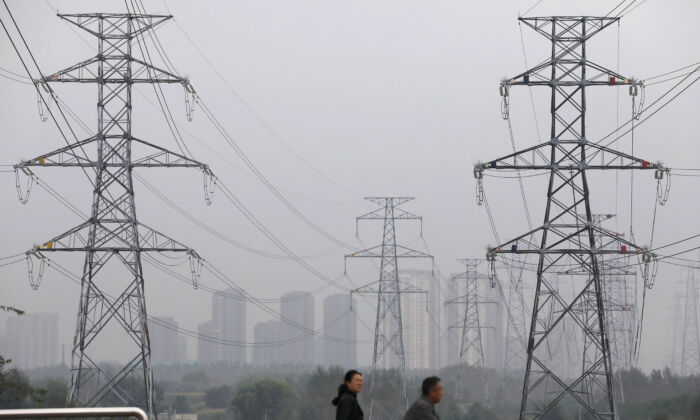 People walk past electricity pylons in Shenyang, Liaoning Province, China, on Sept. 29, 2021. (Reuters/Tingshu Wang)