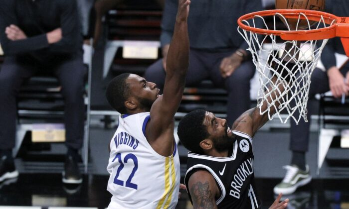 Kyrie Irving #11 of the Brooklyn Nets attempts a layup against Andrew Wiggins #22 of the Golden State Warriors during the second half at Barclays Center on Dec. 22, 2020. (Sarah Stier/Getty Images)