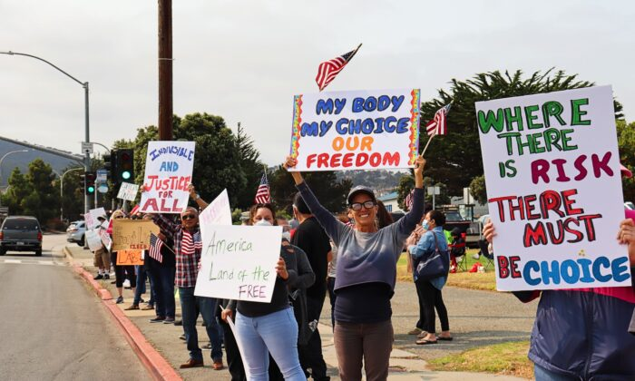 People hold signs calling for freedom of choice during a rally protesting vaccine mandates in Monterey, Calif., on Sept. 26, 2021. (Cynthia Cai/The Epoch Times)