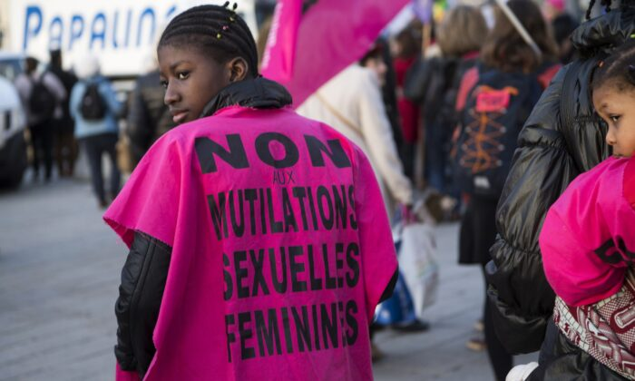 """A woman wears a jersey reading """"No to female genital mutilation"""" during a demonstration to defend women's rights on International Women's Day in Marseille, France, on March 8, 2018. (Bertrand Langlois/AFP via Getty Images)"""