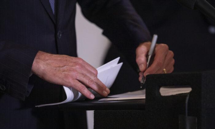 California Governor Gavin Newsom signs multiple bills in Los Angeles on Sept. 29, 2021. (John Fredricks/The Epoch Times)