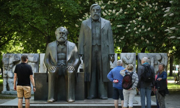 Visitors look at statues of Karl Marx (L) and Friedrich Engels in a park in Berlin, Germany, on May 4, 2018. The illusions that many in the West hold about socialism today mirror the experiences of countless impressionable young people who embraced communism in the last century in the Soviet Union, China, and elsewhere. (Sean Gallup/Getty Images)