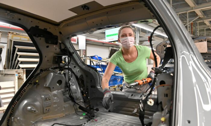 A technician works at the assembly line of Volkswagen's electric ID.3 car in Zwickau, Germany on June 23, 2021. (Matthias Rietschel/Reuters)