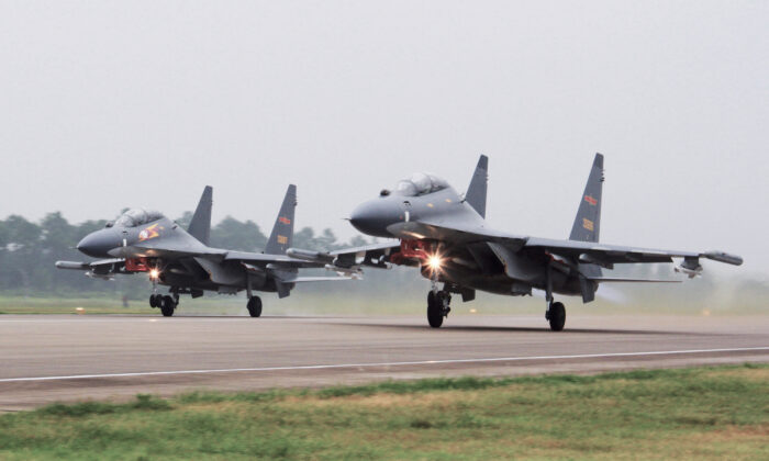 Two Chinese SU-30 fighter jets take off from an unspecified location to fly a patrol over the South China Sea in a file photo. (Jin Danhua/Xinhua via AP)