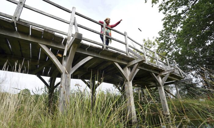 Silke Lohmann of Summers Place Auctions stands on the original Poohsticks Bridge from Ashdown Forest, featured in A.A. Milne's Winnie the Pooh books and E.H. Shepard's illustrations, near its original location in Tonbridge, Kent, England, on Sept. 30, 2021. (Gareth Fuller/PA via AP)