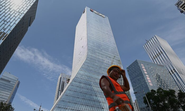 A worker walks in front of Evergrande headquarters in Shenzhen, China, on Sept. 26, 2021.  (Noel Celis/AFP via Getty Images)